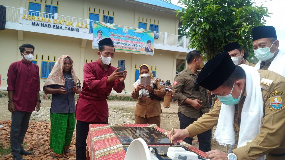 Gubernur Jambi Dr. H Al Haris, S.Sos., MH saat menandatangi prasasti peresmian Asrama Datuk AZA dan Pendopo Datuk Datuk Zainul Abidin, Senin (11/10/2021).